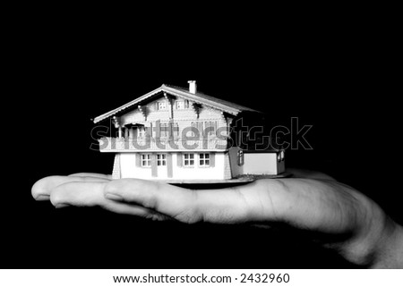 a man is holding a house in his hand - property market