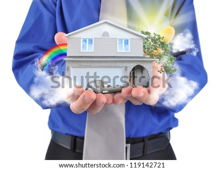 A man is holding a house in his hands with a rainbow and clouds. There is a key for the home ownership.