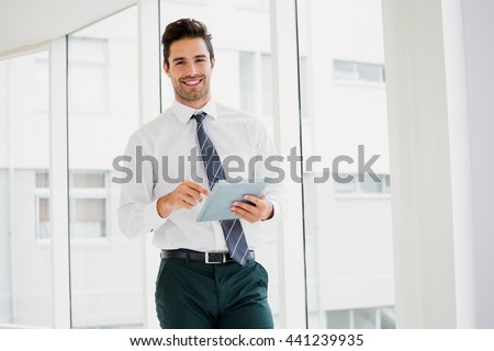 A man is holding a notebook and smiling at office