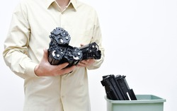 A man is holding cartridges in a close-up group on the background of a container with spent cartridges. The concept of the problem of disposal of harmful chemical waste of office equipment.