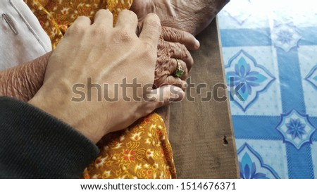 A man is holding the elder's hand with love and care. caring elderly picture.
