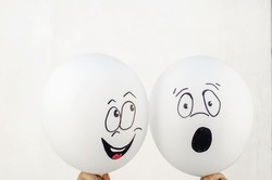 A man is holding two balloons against a light wall. Two white balloons with faces drawn on them. Hand-drawn emotions. Indoors.