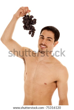 A man is holding up some grapes ready to eat them.