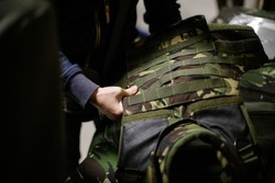 A man is inspecting a bulletproof military vest