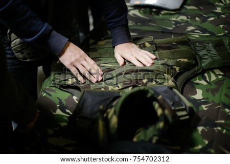 A man is inspecting a bulletproof military vest Stock photo ©