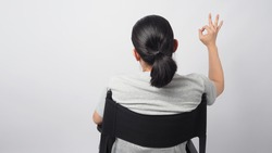 A man is is do a okay hand sign and sitting on director chair.It is white background.It use in cinema or film production.