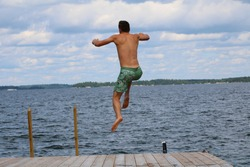 A man is jumping off the dock into the lake. The sky is blue with clouds.