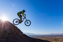 A man is jumping on the bicycle, on the background of blue sky. Sunny autumn day. Mountain bike race. Free space for text.