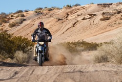 A man is kicking up dust as he rides his motorcycle through the desert