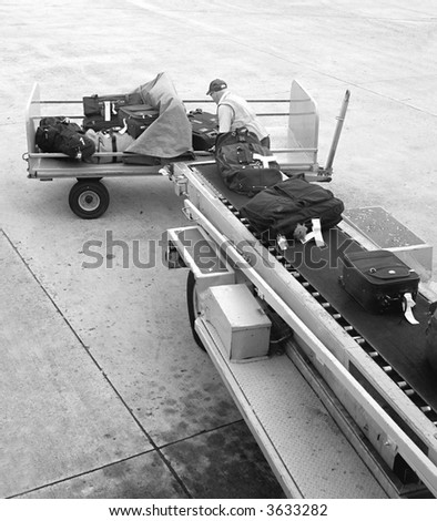 A man is loading luggage onto airplane  - black and white version.