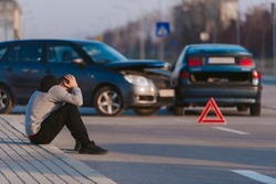 A man is looking desperate after two cars crashing on the road by his fault