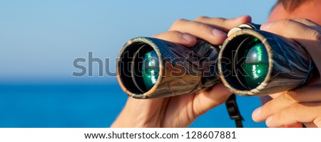 a man is looking to the binocular on sea