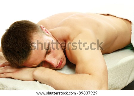 A man is lying and relaxing in spa center isolated on white background