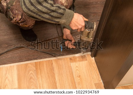 A man is making a threshold on the floor #1022934769