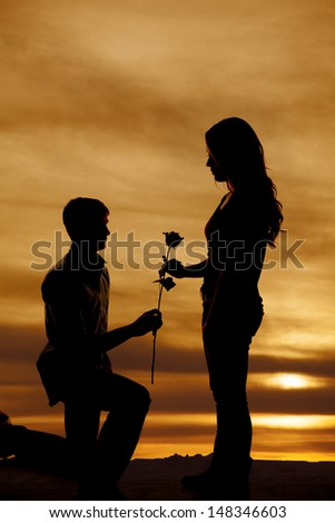 A man is on one knee handing a woman a rose in the sunset. - stock photo