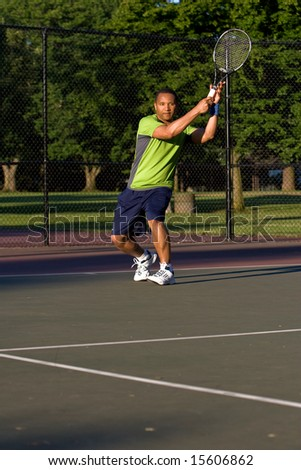 A man is outside on a tennis court playing tennis.  He is looking at the tennis ball.  Vertically framed shot.
