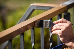 a man is painting a metal railing with copper varnish, close up outdoor shot