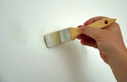 A man is painting a wall in white color with a paintbrush. He is improving his  home, removing the spots on the wall. He works in delicate movements and prepares the wall for the final layer of paint.