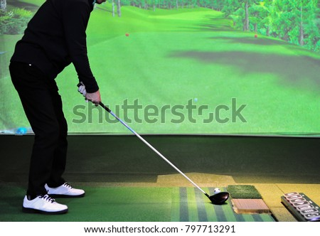 A man is playing golf at ? screen golf driving range  #797713291