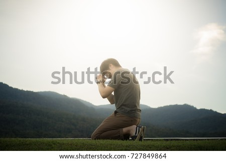 A man is praying to God on the mountain.