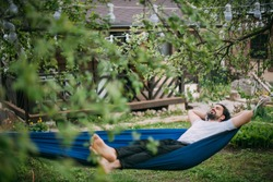 A man is resting in a hammock in a country house. A young guy lies in a hammock, dozing outdoors in the summer in the green of trees in the country
