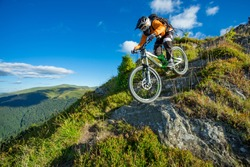 A man is riding bicycle, on the background of mountains and blue sky. Beautiful summer day. Mountain bike race