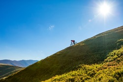 A man is riding enduro bicycle, on the background of mountains and blue sky. Beautiful summer day. Mountain bike race. Free space for text.