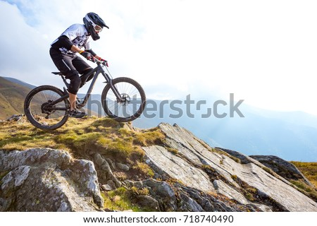 A man is riding enduro bicycle, on the background of mountains. Beautiful summer day.