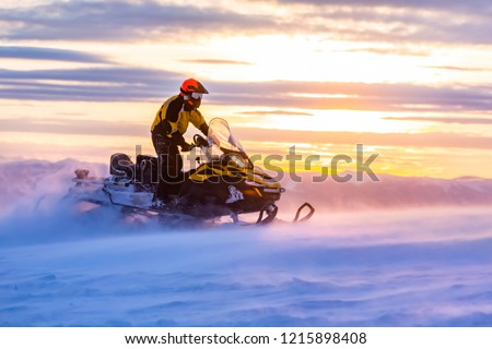 A man is riding snowmobile in mountains. Beautiful morning light. Blue shadows. Stock photo ©