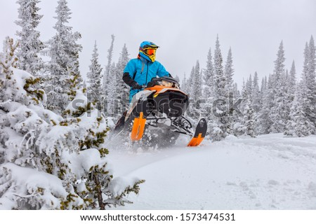A man is riding snowmobile in mountains. jump on a snow bike. pilot on a sports snowmobile in a mountain forest. The concept of skidooking. rider in a bright suit on a colorful snowy moto. Hi quality Stock photo ©