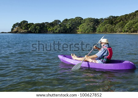 A man is rowing in the open sea a purple kayak.