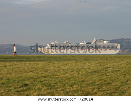 A man is seemingly followed by a cruise ship as he takes a walk on San Francisco's Crissy Field. - stock photo