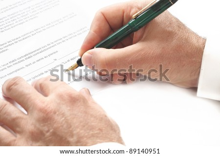 A man is signing a contract with a pen