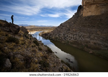 A man is silhouetted in Santa Elena canyon as he looks down at three canoes in the Rio Grande, Big Bend National Park, Texas.  The left side of the river is the United States, on the right is Mexico.