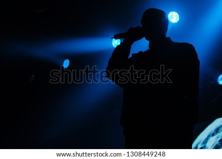 A man is singing on the stage. Dark silhoette. Blue indigo background. A concert of a famous artist #1308449248