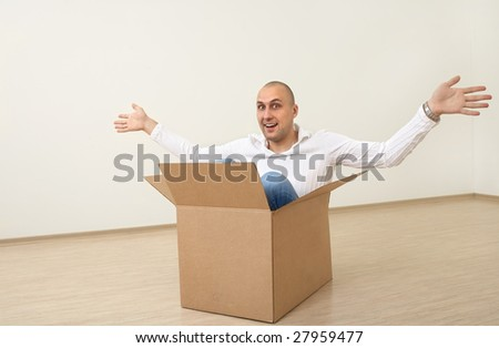A man is sitting in an empty box in a new flat