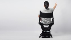 A man is sitting on director chair and hand's is pointing with clapper board put on the ground.It is white background.