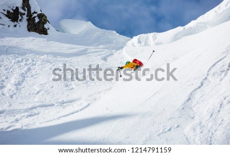 A man is skiing down the hill on the steep slope in Alps.  #1214791159