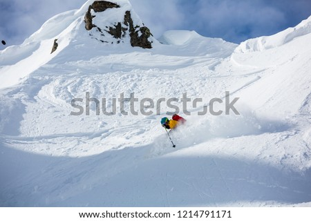 A man is skiing down the hill on the steep slope in Alps.  #1214791171
