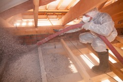A man is spraying ecowool insulation in the attic of a house. Insulation of the attic or floor in the house