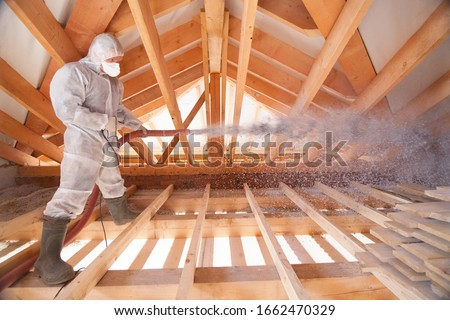 A man is spraying ecowool insulation in the attic of a house. Insulation of the attic or floor in the house Stock photo ©
