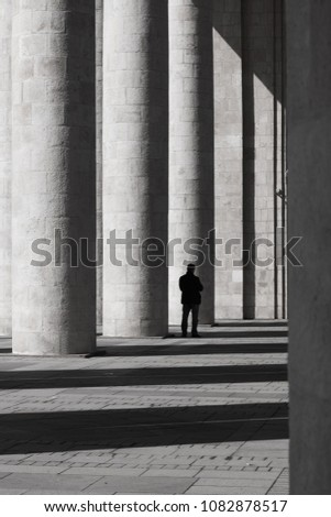 A man is standing by a white column #1082878517