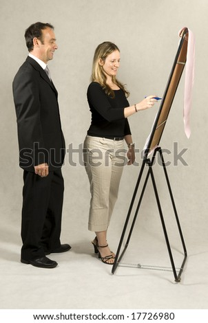 A man is standing next to a young woman who is drawing on a large board.  It looks as if she is drawing a business model.  They are smiling and looking at the board.  Vertically framed shot.