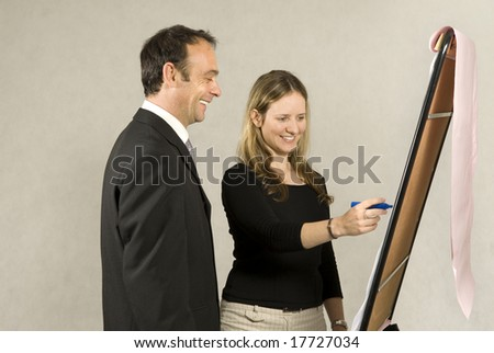 A man is standing next to a young woman who is drawing on a large board.  It looks as if she is drawing a business model.  They are smiling and looking at the board.  Horizontally framed shot.