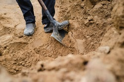 A man is standing on a pile of sand and digging with a steel shovel.