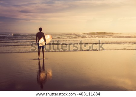 stock photo a man is standing with a surf in his hands on the sea shore 403111684 - Каталог — Фотообои «Море, пляж»