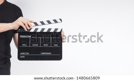A man is standing with hands is holding black Clapperboard or movie slate. it use in video production ,film, cinema industry.It is white background. #1480665809
