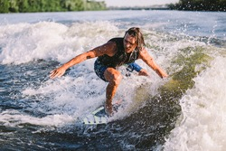 A man is surfing on a surfboard drawn by a motor boat above the wave of the boat. Weixerfer is engaged in surfing, entertainment, leisure, water sports. Athlete glides on the waves on the board.