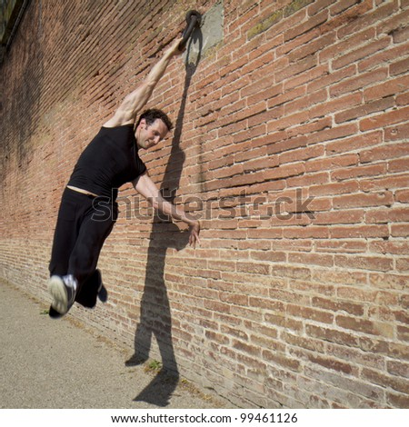 A man is swinging, hanged at a ring. He is exercising along a wall of red bricks.