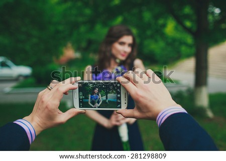 a man is taking pictures of a beautiful girl on his phone